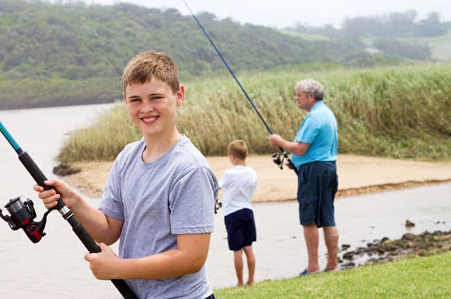 boy fishing with brother and grandpa