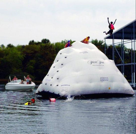 Guy jumping off huge inflatable ice burg into lake
