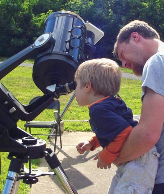 Dad lifts son up to see through star telescope